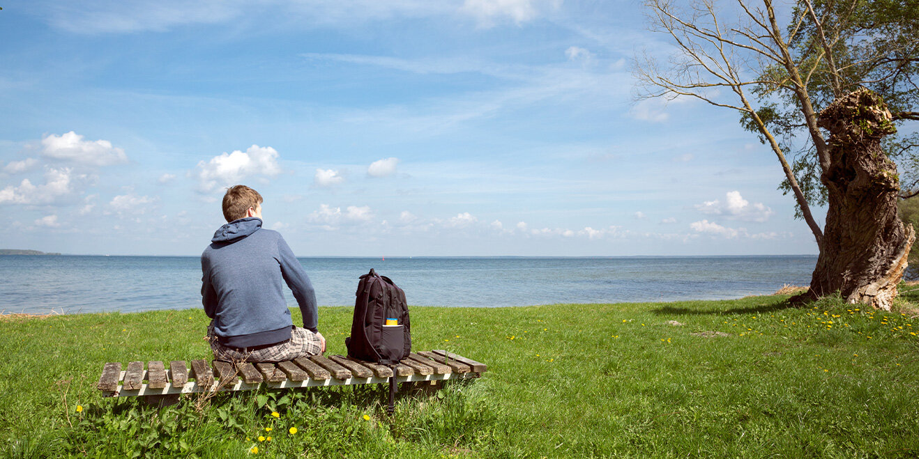 Wanderer auf einer Bank am Müritz-See