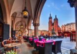 Machen Sie eine Pause unter den historischen Tuchhallen und beobachten Sie das bunte Treiben auf dem Marktplatz von Krakau.