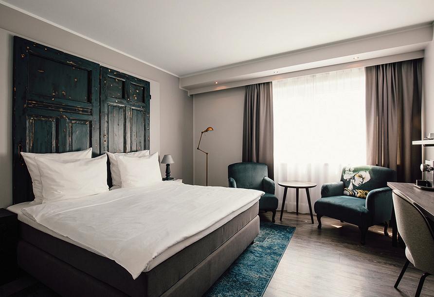 Modern eingerichtetes Doppelzimmer mit gemütlichem Bett und Sitzecke.