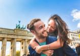 Verliebtes Paar vor dem Brandenburger Tor bei Sonnenschein.