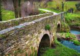 Mittelalterliche Brücken über kleine Flüsse säumen Ihren Weg, wie hier in Sarria.