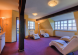 Ruheraum mit lila Teppichboden und weißen Ruheliegen.