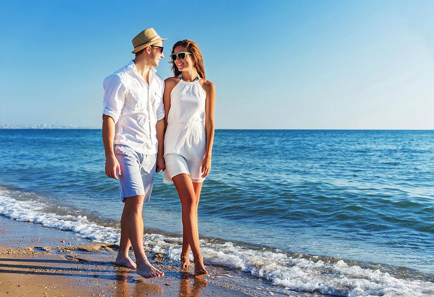 Paar läuft am Strand entlang.