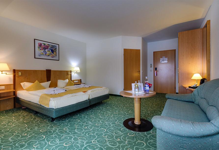 Gemütliches Doppelzimmer mit großem Bett und Sitzecke.
