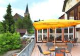 Terrasse vom Harzhotel Güntersberge mit gelben Sietzgelegenheiten und gelben Sonnenschirmen.