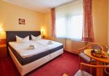 Gemütliches Hotelzimmer mit großem Doppelbett und rotem Teppichboden.