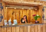 Lächelnde Frau an der mit Holz verkleideten Rezeption vom Harzhotel Güntersberge.