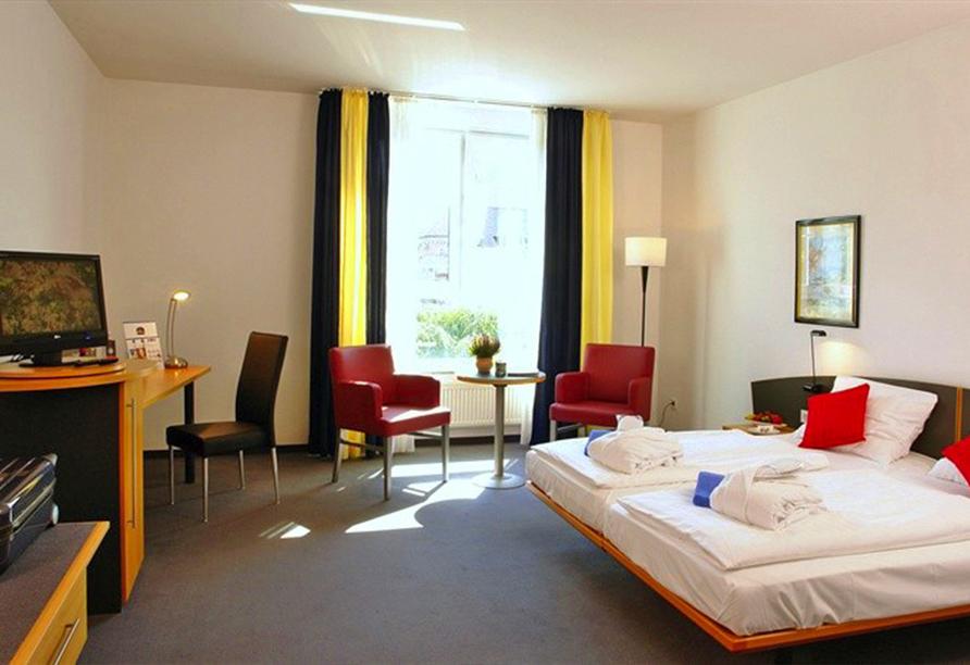 Beispiel für ein Doppelzimmer mit gemütlichem Bett und grauem Teppichboden.