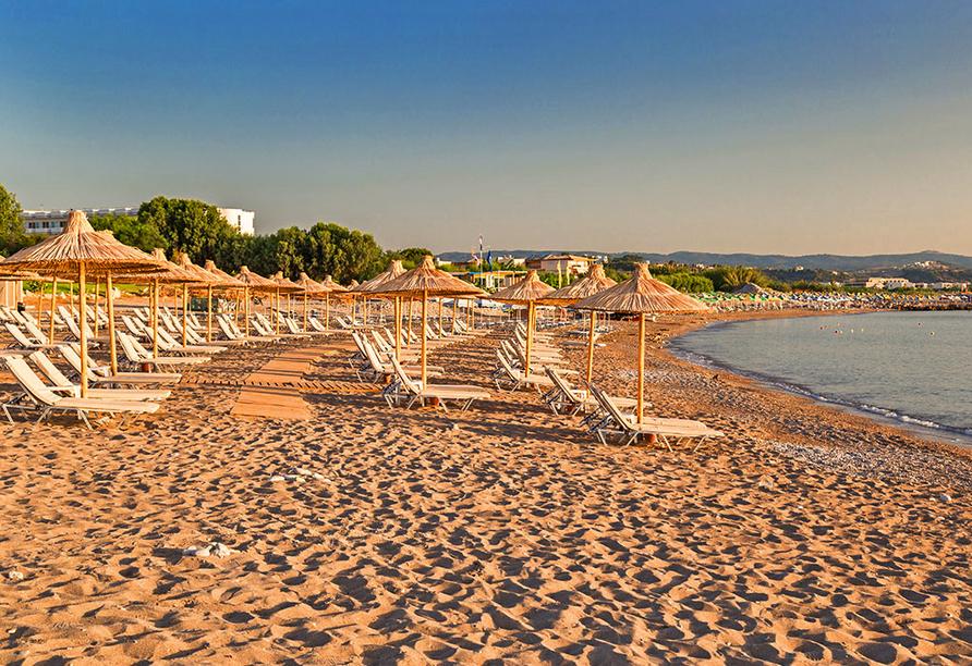 Strand von Kolymbia mit Sonnenliegen und -schirmen.