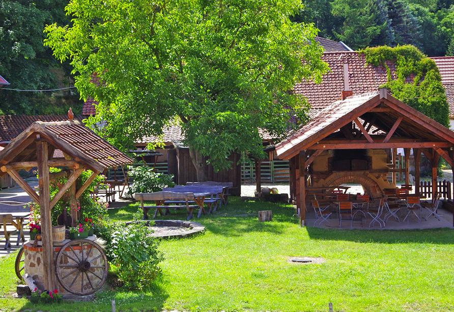 Idyllishcer Innenhof mit viel Grün und Biergarten in der Mitte.
