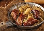 Schmorwurst und Sauerkraut in der Pfanne.