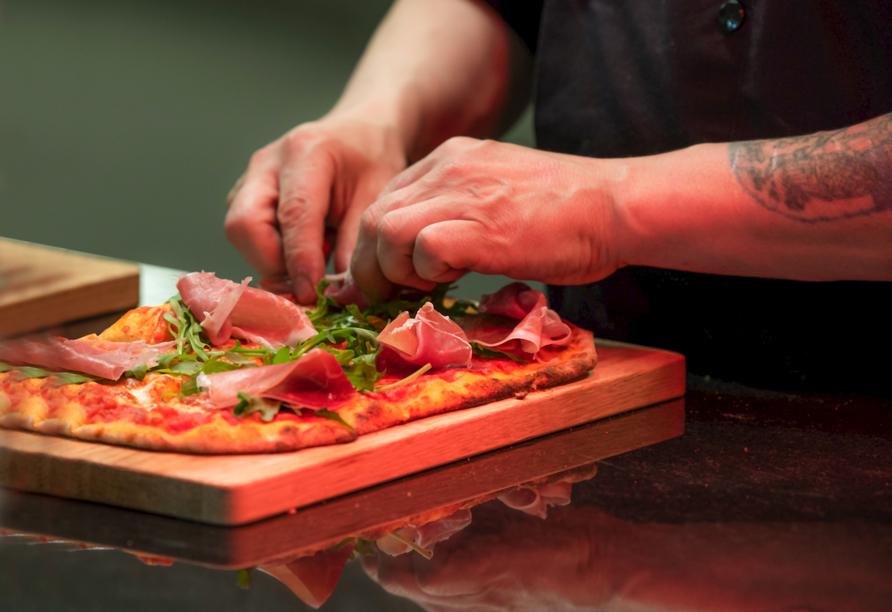 Frisch belegte Pizza mit Rucola und Schinken.