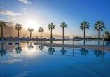 Palmen rund um den Außenpool verbreiten die richtige Urlaubsstimmung.