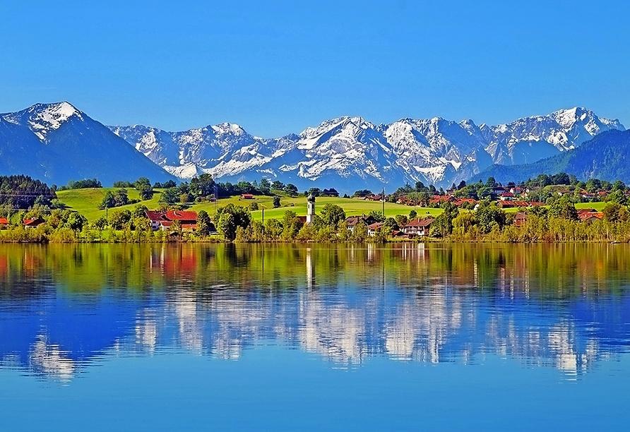 Der Riegsee liegt traumhaft vor der imposanten Bergwelt der Bayerischen Alpen.