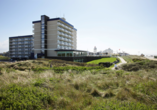 Dünen, feiner Sandstrand und das Meer umgeben ihr Hotel.