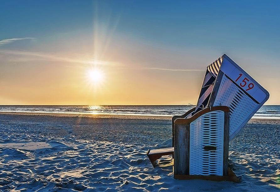 Erleben Sie wunderschöne Sonnenuntergänge in einem Strandkorb.