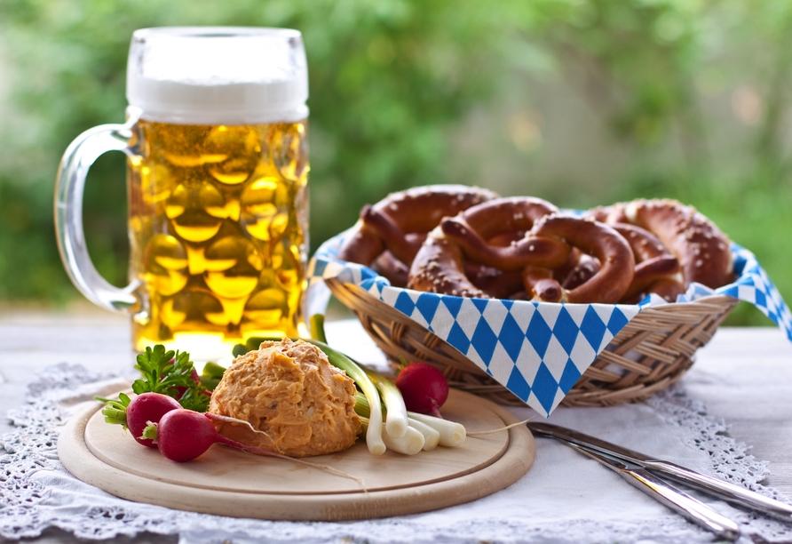Genießen Sie bayerische Spezialitäten wie Obatzda mit Brezel und Bier.