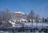 Blick auf Burg Schönfels in verschneiter Winterlandschaft.