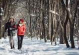 Unternehmen Sie einen entspannten Spaziergang durch die verschneite Winterlandschaft.