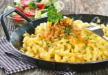 Lassen Sie sich beispielsweise mit Käsespätzle im Pfännchen mit Röstzwiebeln und Salat verwöhnen.