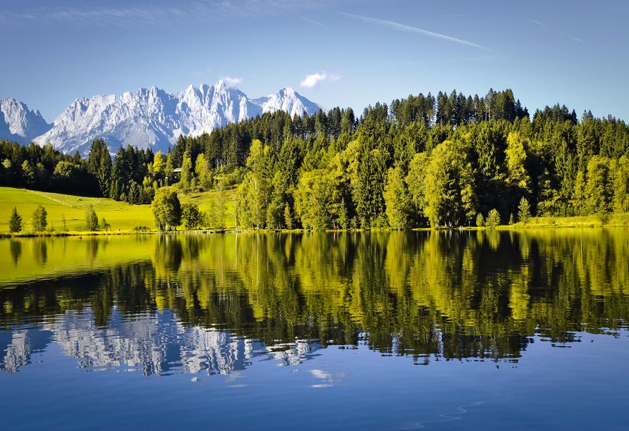 Sonnen Sie sich am Schwarzsee und genießen Sie den einmaligen Blick auf den Wilden Kaiser – und das schöne Spiegelbild im See.