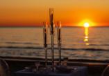 Wie wäre es mit einem Abendessen am Strand mit Blick auf den Sonnenuntergang über dem Meer?